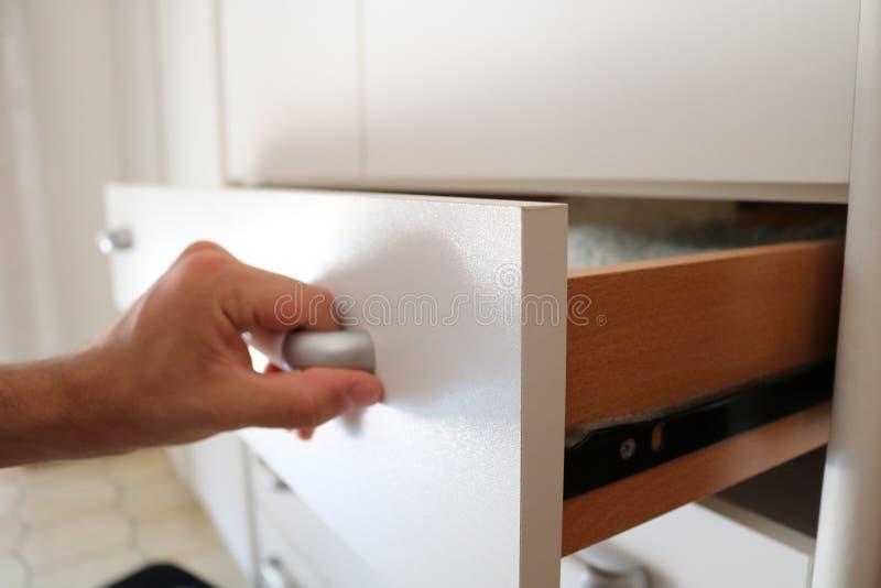 O homem abre a gaveta do vestuário, fim da mão acima fotos de stock