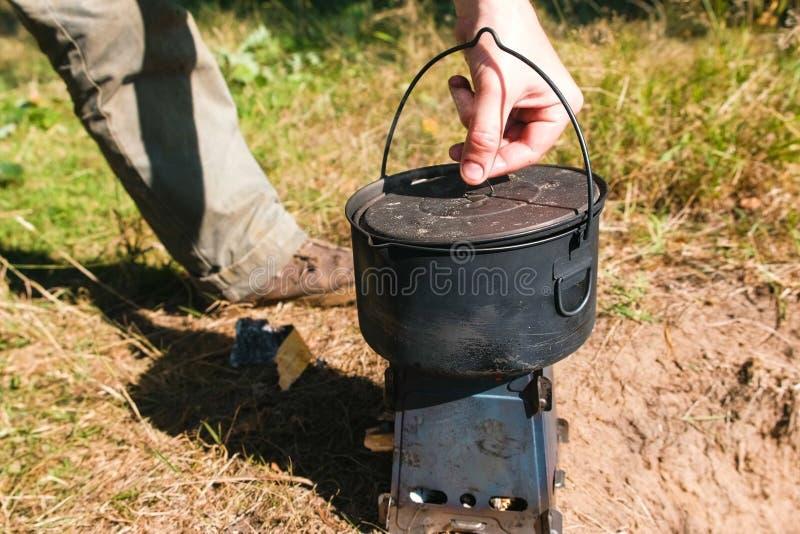 O homem abre um potenciômetro em um fogão da fornalha do acampamento do metal em madeiras fora Close-up da mão fotos de stock