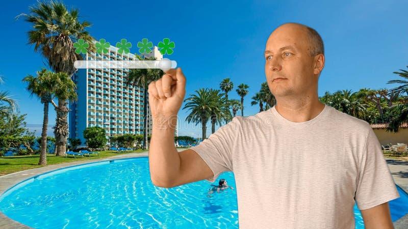 O homem adulto em um fundo de uma piscina põe uma avaliação dos serviços Uma avaliação dos lugares para realizar-se de fotos de stock royalty free