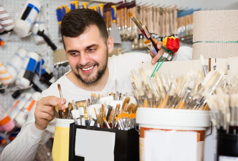 O homem adulto está decidindo na melhor escova para pintar e decorar imagem de stock royalty free