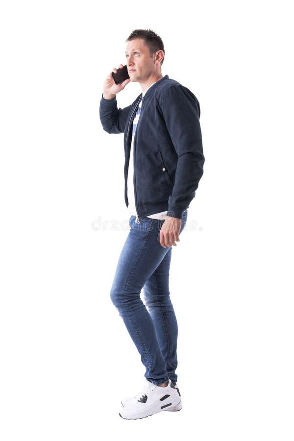 O homem adulto novo da virada confusa anda e fala no telefone celular que olha acima fotografia de stock royalty free