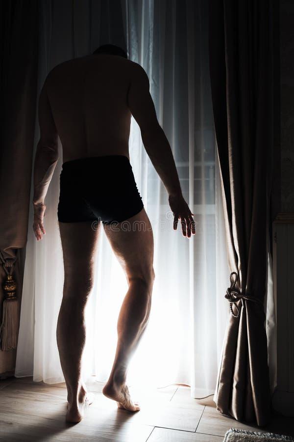 O homem adulto novo está perto da janela de incandescência foto de stock royalty free