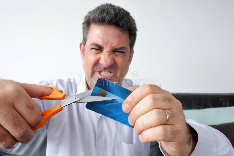 O homem adulto que corta um cartão de crédito com um par de scissor imagens de stock