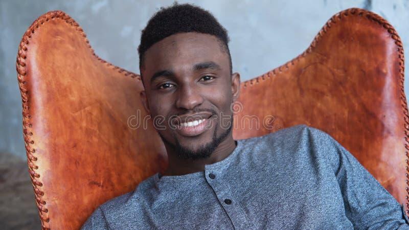 O homem africano com uma barba está sentando-se na cadeira, está sorrindo-se e está olhando-se em linha reta na câmera Sentimento fotografia de stock