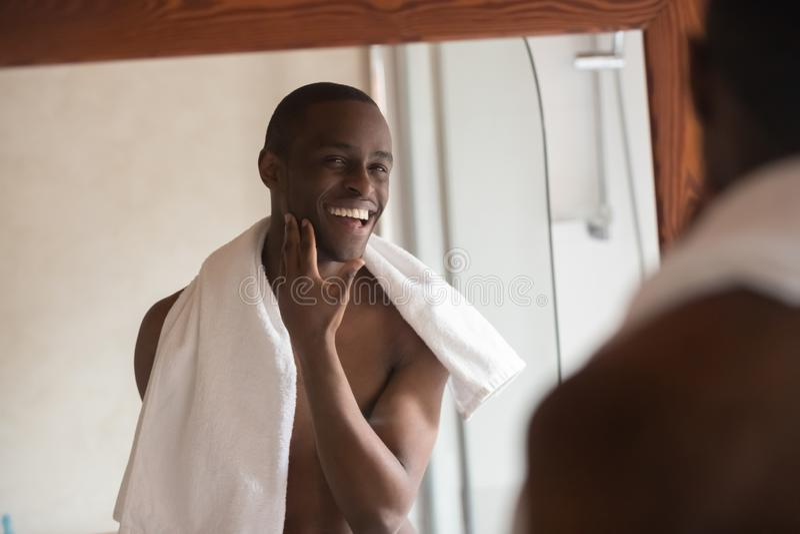 O homem africano considerável barbeado que olha no espelho sente satisfeito imagem de stock