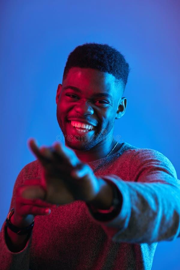 O homem africano de riso estica para fora a m?o sugere-nos para juntar-se contra a parede azul foto de stock royalty free
