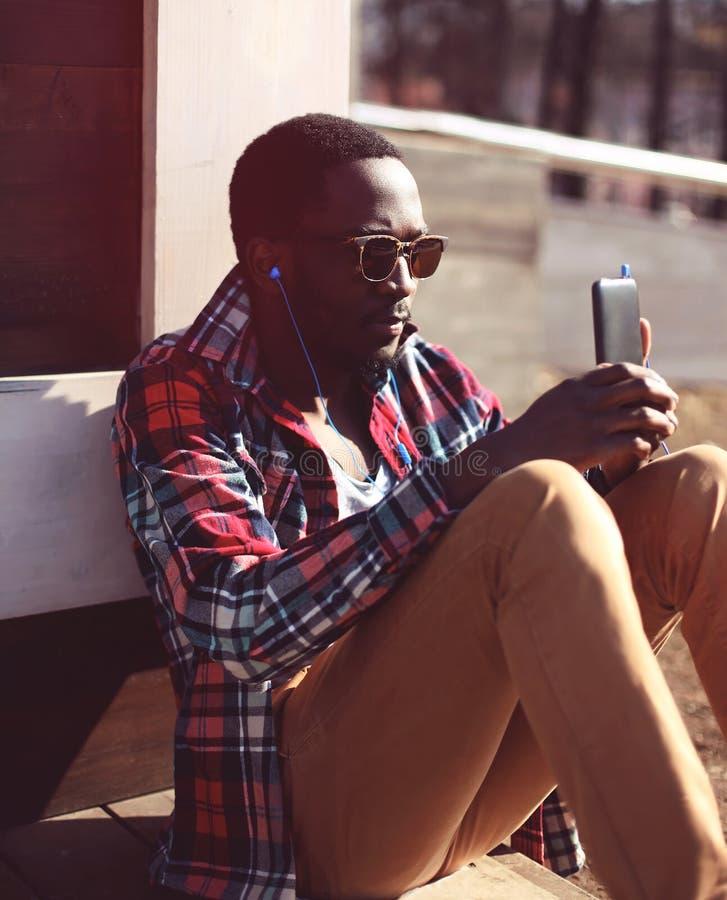 O homem africano novo à moda escuta a música e smartphone da utilização, imagens de stock
