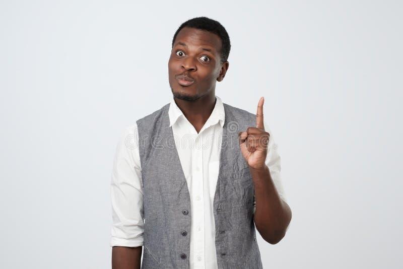 O homem africano novo aumenta o indicador tão obtém ideia como fazer projeto interessante fotos de stock