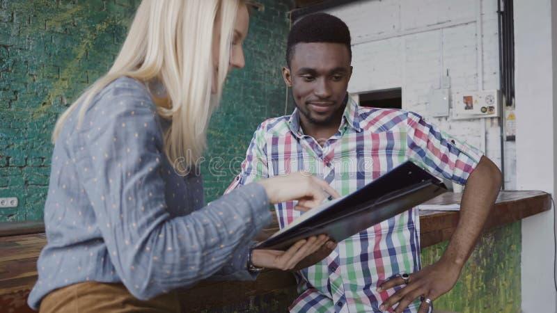 O homem africano novo e a mulher caucasiano sentam-se perto do contador da barra no escritório moderno e em discutir os originais imagens de stock