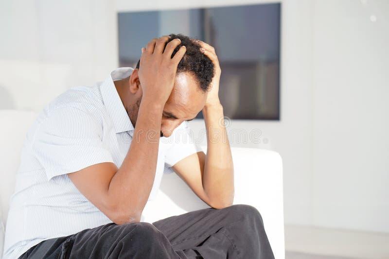 O homem africano triste encontra-se na cama imagem de stock royalty free
