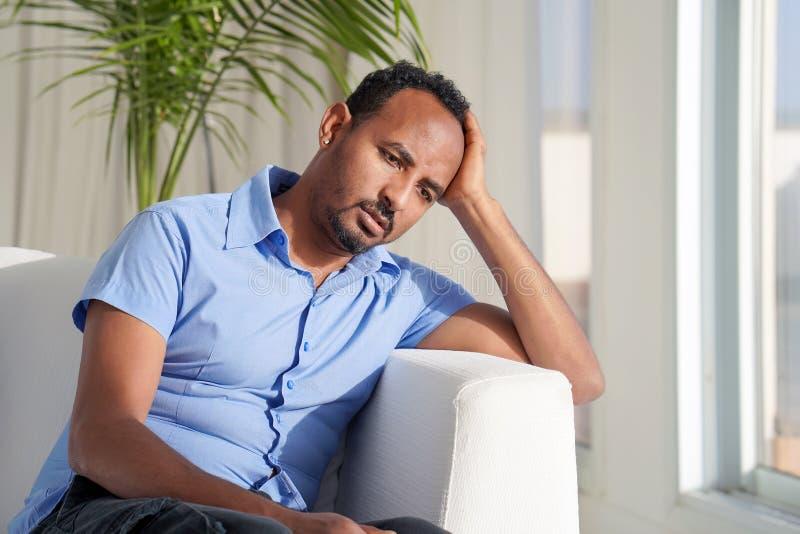 O homem africano triste encontra-se na cama imagem de stock