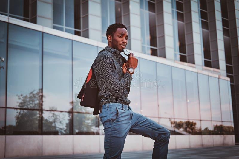 O homem afro-americano atrativo está estando perto de seu escritório fotos de stock