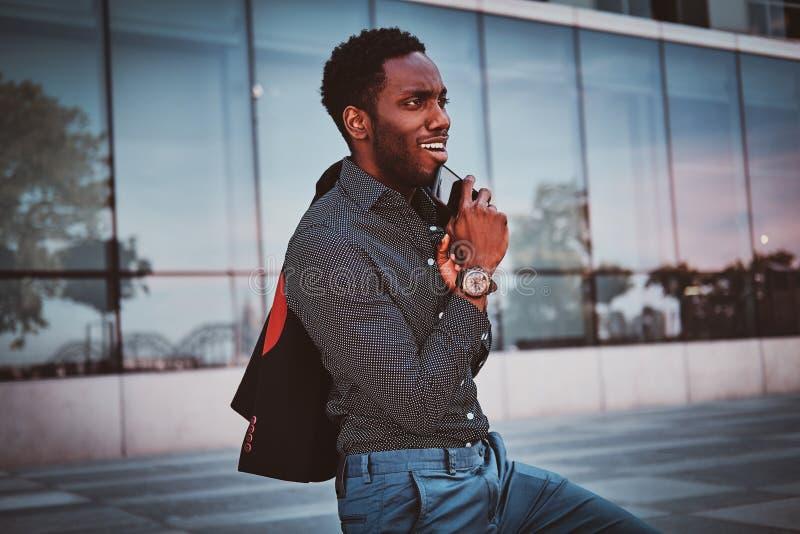 O homem afro-americano atrativo está estando perto de seu escritório imagem de stock royalty free