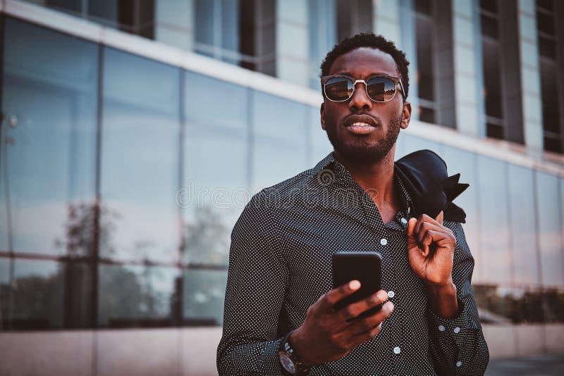 O homem afro-americano atrativo está estando perto de seu escritório fotos de stock royalty free