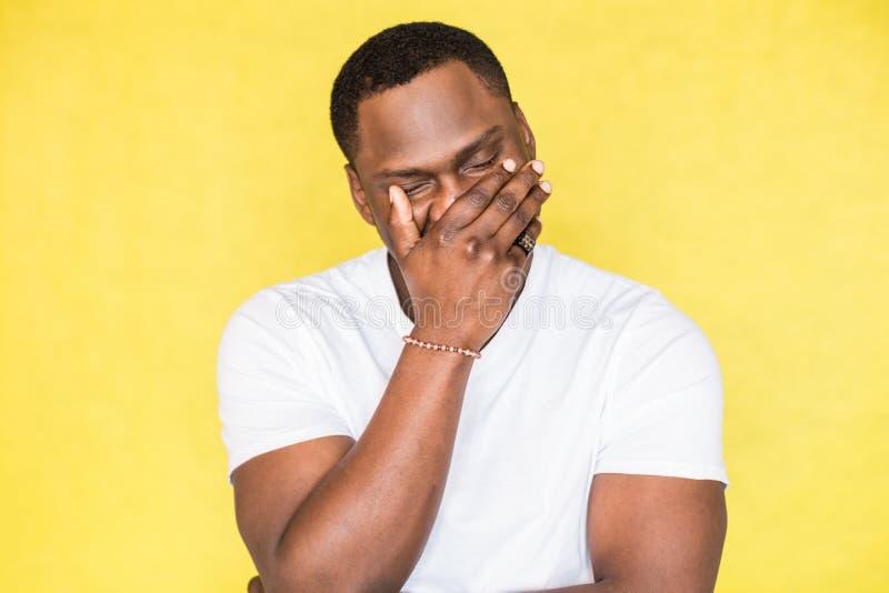 O homem afro-americano cobriu sua cara com sua mão imagem de stock royalty free