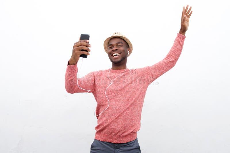 O homem afro-americano feliz com braço aumentou ao escutar a música com telefone celular e fones de ouvido fotografia de stock royalty free