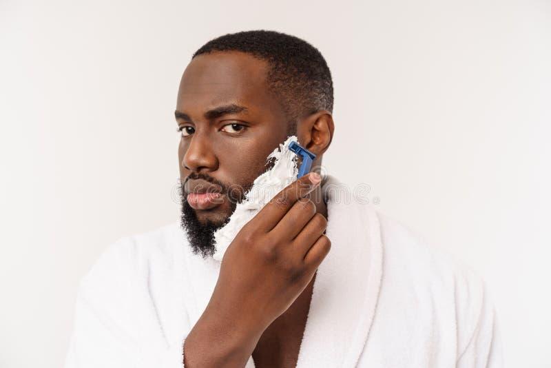 O homem afro-americano mancha o creme de rapagem na cara pela escova de rapagem Higiene masculina Isolado no fundo branco est?dio fotografia de stock royalty free