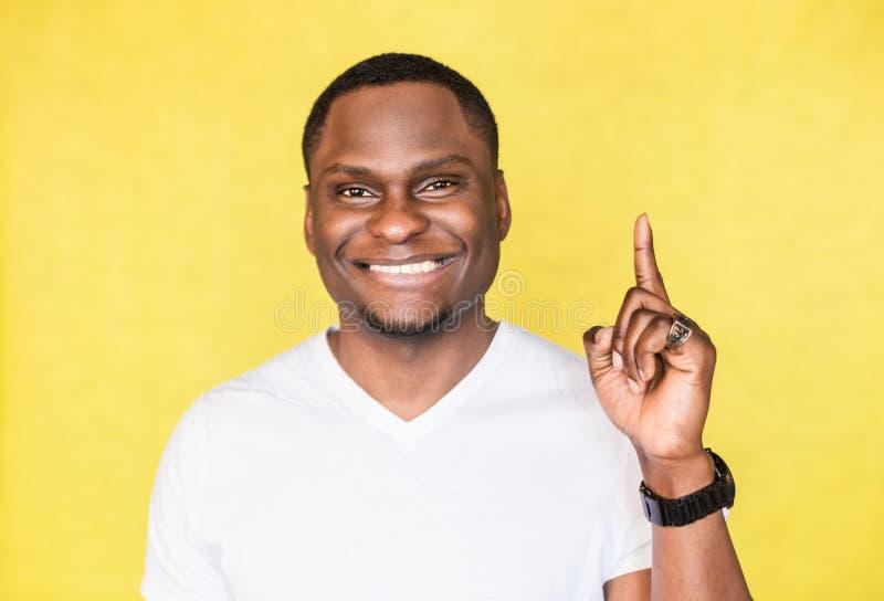 O homem afro-americano novo aumenta o indicador tão obtém boa ideia foto de stock royalty free