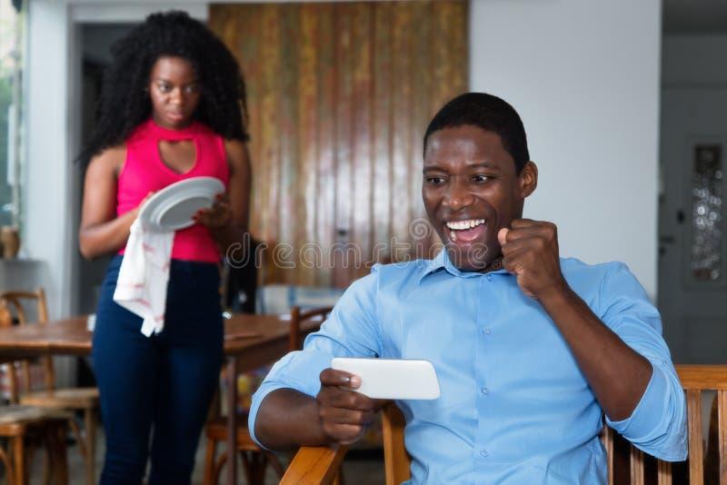 O homem afro-americano preguiçoso não gosta do trabalho doméstico imagem de stock