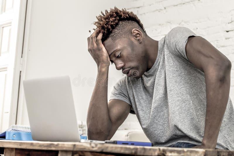 O homem afro-americano preto desesperado e oprimido novo do estudante no trabalho do esforço em casa forçado com laptop preocupou imagens de stock