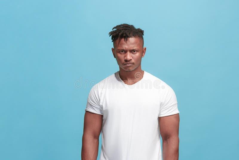 O homem afro irritado emocional novo no fundo azul do estúdio fotos de stock royalty free