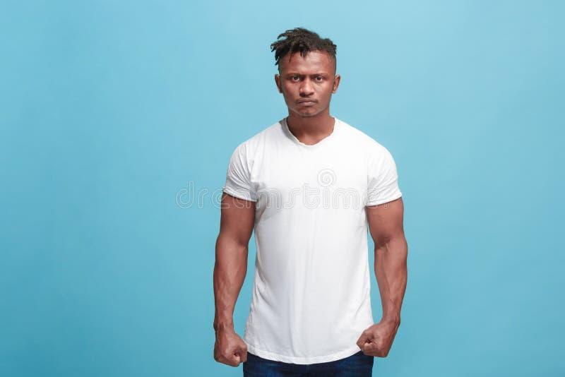 O homem afro irritado emocional novo no fundo azul do estúdio foto de stock royalty free