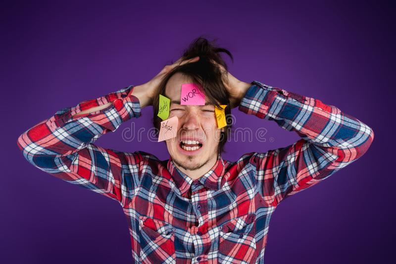 O homem agarra sua cabeça, grita com seus olhos fechados e sua boca aberta, etiquetas em sua cara Um homem é chocado pelo seu fotos de stock royalty free
