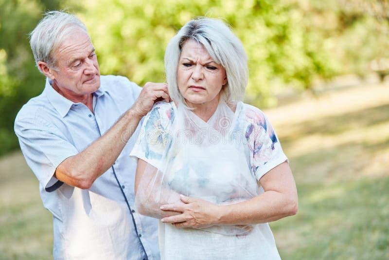 O homem ajuda a mulher com braço quebrado fotografia de stock royalty free