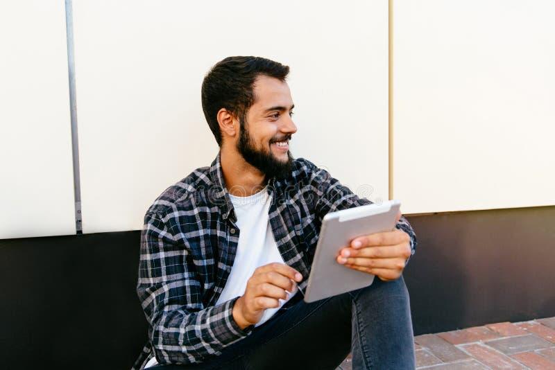 O homem alegre guarda uma tabuleta digital, ao sentar-se no ar livre à terra fotografia de stock royalty free