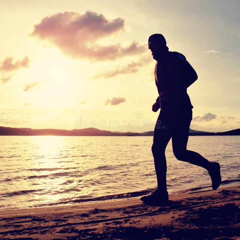 O homem alto com óculos de sol e o tampão escuro está correndo na praia no por do sol do outono imagem de stock