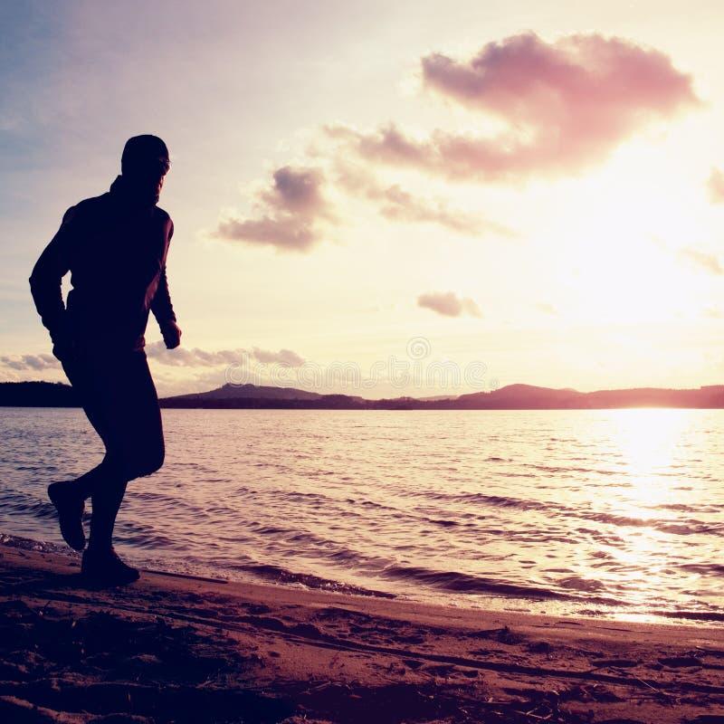 O homem alto com óculos de sol e o tampão escuro está correndo na praia no por do sol do outono imagens de stock royalty free