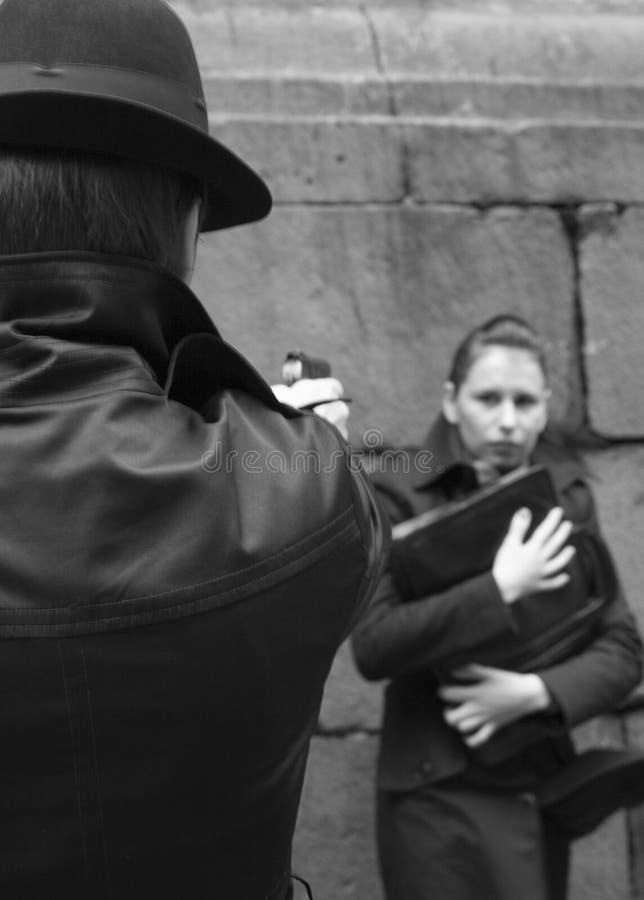 O homem ameaça a mulher com uma pistola foto de stock