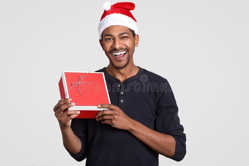 O homem americano do africano negro alegre leva a caixa atual vermelha, veste o chapéu de Santa Claus, feliz receber o presente d imagem de stock
