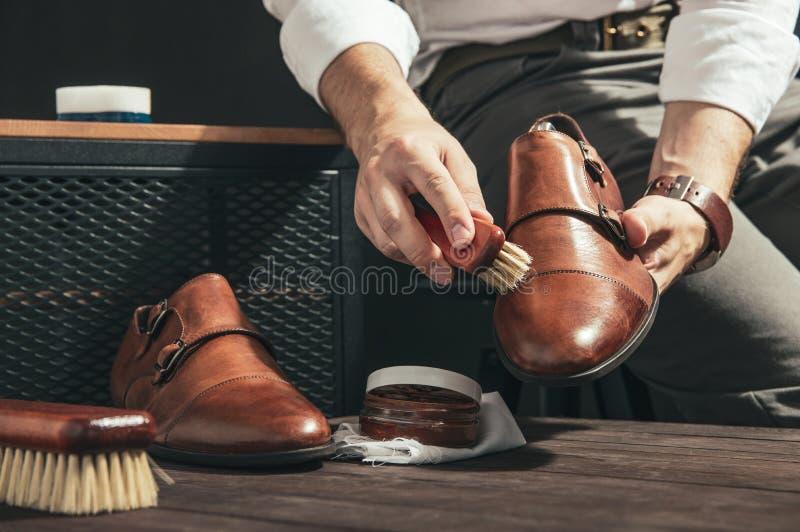 O homem aplica o polimento de sapata fotografia de stock royalty free