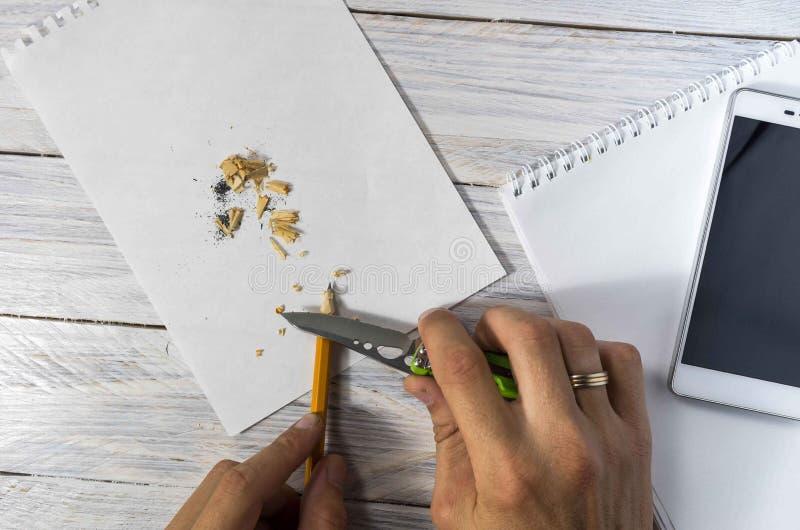 O homem aponta um lápis com uma faca no local de trabalho Textura e fundo branco imagem de stock