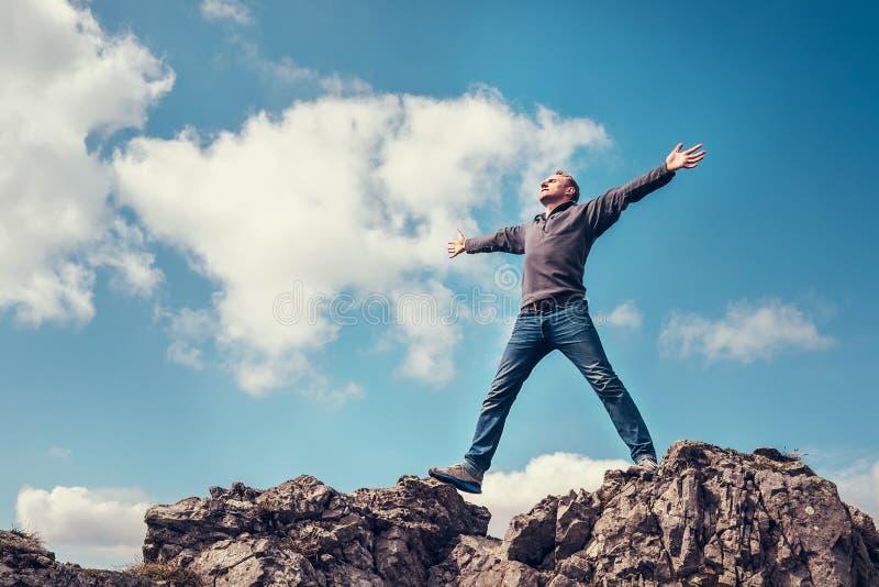 O homem aprecia com sensação da liberdade na parte superior da montanha imagem de stock