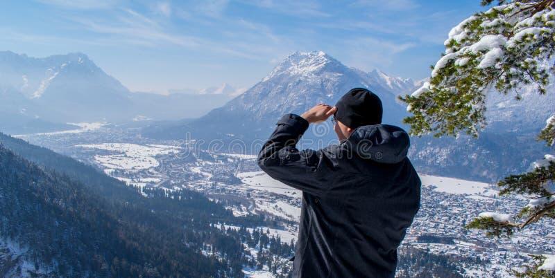O homem aprecia a vista e olha para baixo em Garmisch-Partenkirchen e em Farchant fotografia de stock royalty free