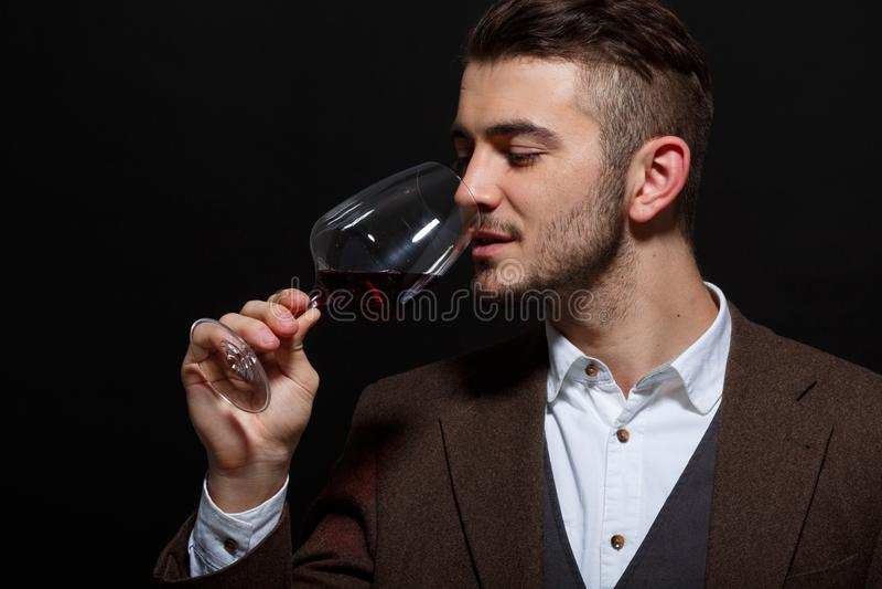 O homem apresentou um vidro do vinho a sua boca em um fundo preto fotos de stock royalty free