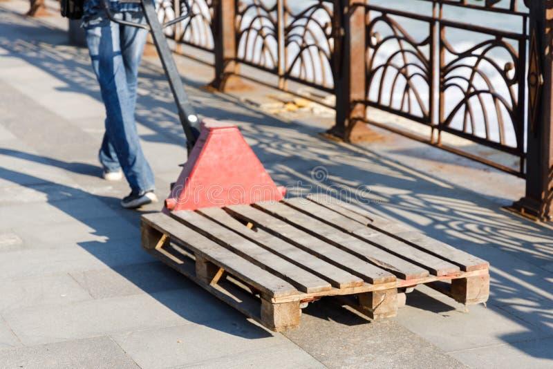 O homem apressa-se ao cliente com um caminh?o de p?lete da m?o para levar cargas pesadas e bagagem imagens de stock royalty free