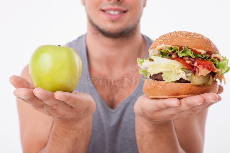 O homem apto dos jovens está fazendo decisões sobre o alimento foto de stock