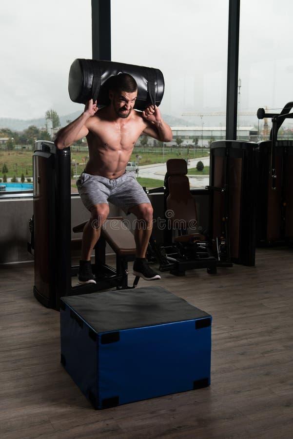 O homem apto dos jovens que faz a caixa salta no Gym foto de stock royalty free