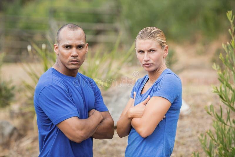 O homem apto e a mulher que estão com braços cruzaram-se durante o treinamento de campo de treinos de novos recrutas fotos de stock