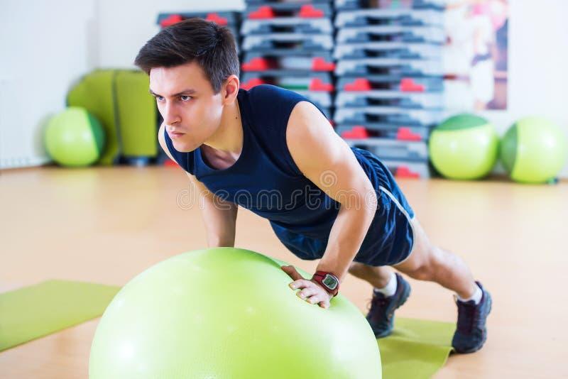 O homem apto que exercita com fazer para fora de braços do exercício da bola do exercício do treinamento do tríceps e do bíceps e imagens de stock
