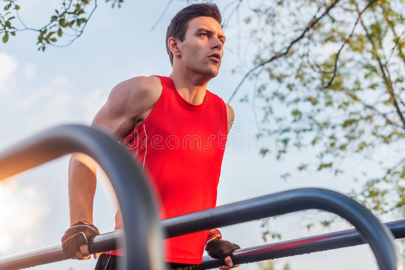 O homem apto que faz o tríceps mergulha em barras paralelas no parque que exercita fora foto de stock