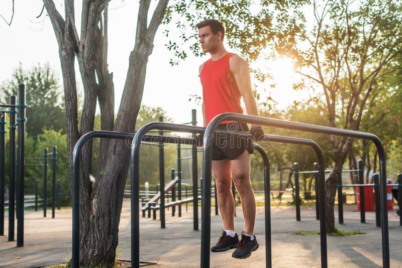 O homem apto que faz o tríceps mergulha em barras paralelas no parque que exercita fora imagens de stock
