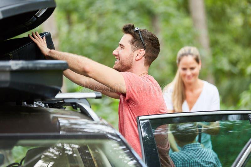 O homem armazena a bagagem na caixa do telhado no carro foto de stock
