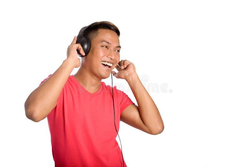 O homem asiático dança enquanto escuta seus auscultadores. imagens de stock