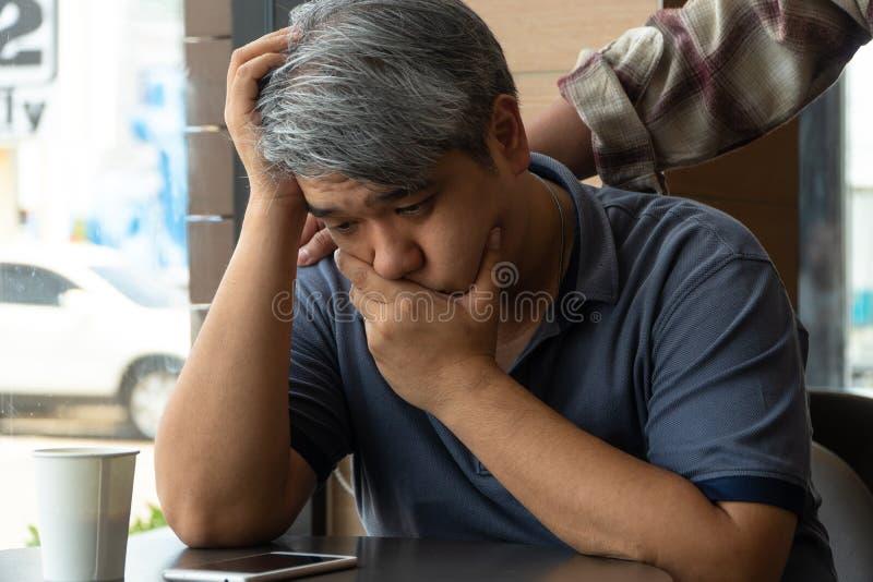 O homem asiático de meia idade 40 anos velho, forçado e cansado, está sentando-se no restaurante do fast food e tem os amigos que imagens de stock royalty free