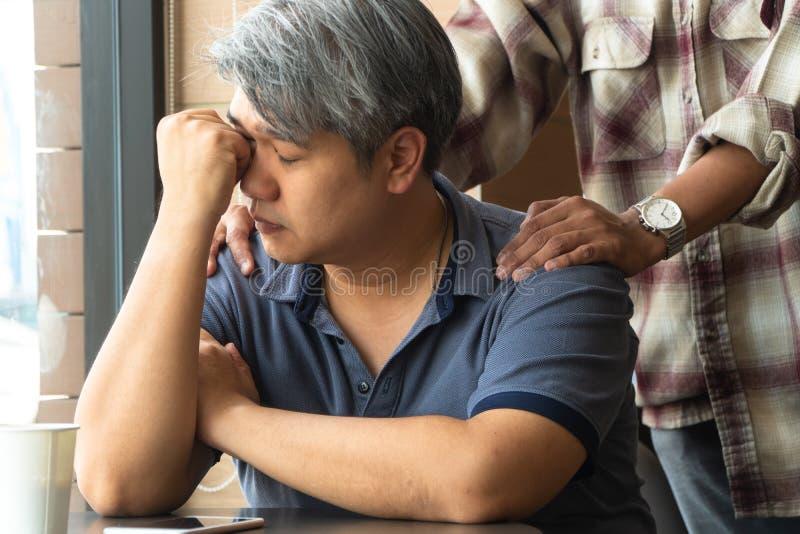 O homem asiático de meia idade 40 anos velho, forçado e cansado, está sentando-se no restaurante do fast food e tem os amigos que foto de stock