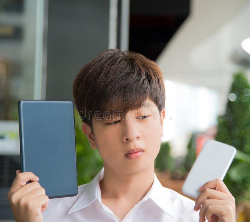 O homem asiático decide e hesita usar dispositivos espertos imagens de stock